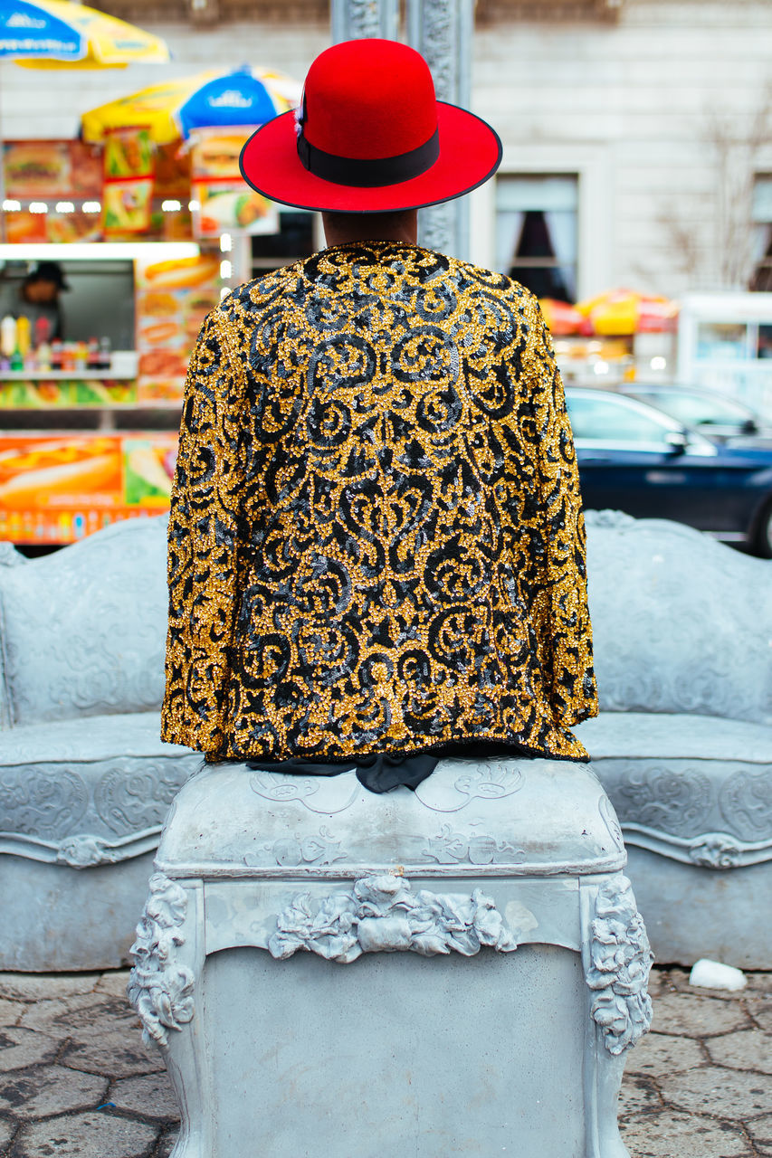 Rear View Of Woman Sitting On Seat Against Market