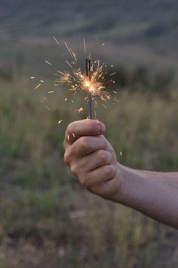 Cropped hand holding illuminated sparkler