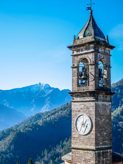 Tower Time Architecture Clock Clock Tower Sky Built Structure Building Exterior Blue Building Mountain Nature Travel Destinations Day The Past No People History Bell Tower - Tower Clear Sky Religion Outdoors Clock Face Minute Hand
