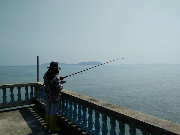 Man fishing by sea against clear sky