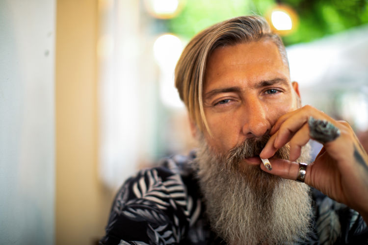 Attractive hipster with a beard is smoking a cigarette in a coffee shop Cigrette Smoke Smoke - Physical Structure Smoking Bad Habit Beard Bearded Rings Tattoo Hairstyle Men Hipster Outdoors Outdoor Photography Sitting City Urban Close-up Smiling Portrait Model Modern Background Defocus person People