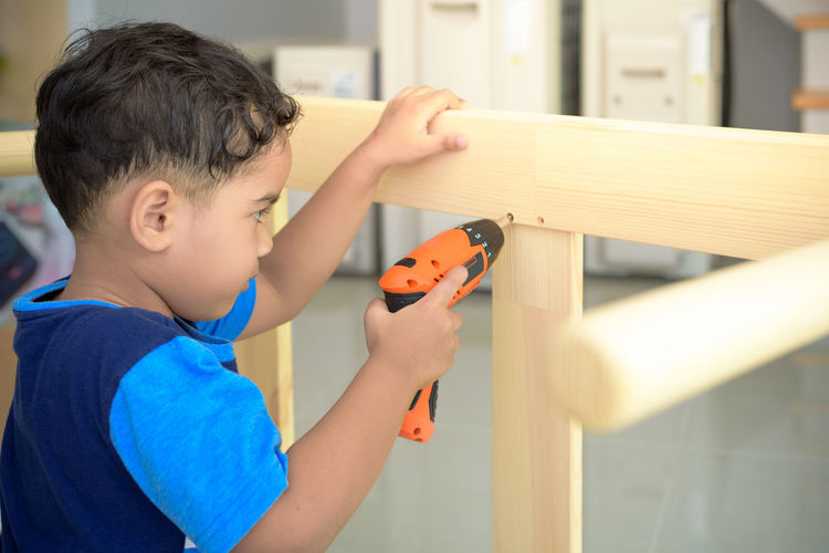 Boy drilling wood at home