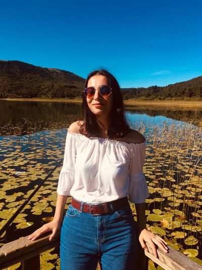 Portrait of young woman wearing sunglasses while standing by lake against blue sky
