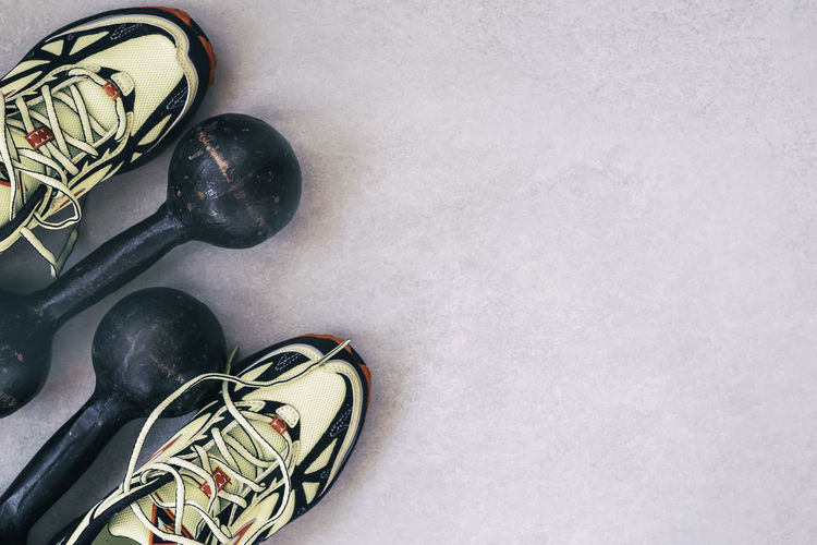 Sneakers and old dumbbells, a top view, the concept of healthy lifestyle. Sports background, copy space High Angle View No People Shoe Sport Close-up Still Life Directly Above Sports Equipment Indoors  Copy Space Shoelace Black Color Sneakers Dumbbells Top View Healthy Lifestyle