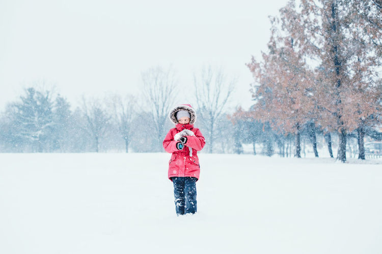 Girl standing on snow covered land