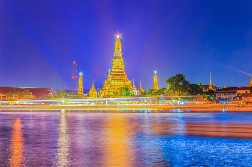 Beautiful cityscape view of Wat Arun Rajwararam temple with light trail from the Chao Phraya river cruises and light shows at night, the popular tourist attraction and one of the symbols of the city. Wat Arun Wat Arun (Temple Of Dawn) Wat Arun Ratchawararam Ratchawarama Wat Arun Temple Wat Arun Temple, Thailand Wat Arun, Bangkok Wat Arun Thailand Architecture Building Exterior Built Structure City Illuminated Nature Night No People Outdoors Place Of Worship Reflection Religion Sky Spirituality Travel Travel Destinations Water Waterfront