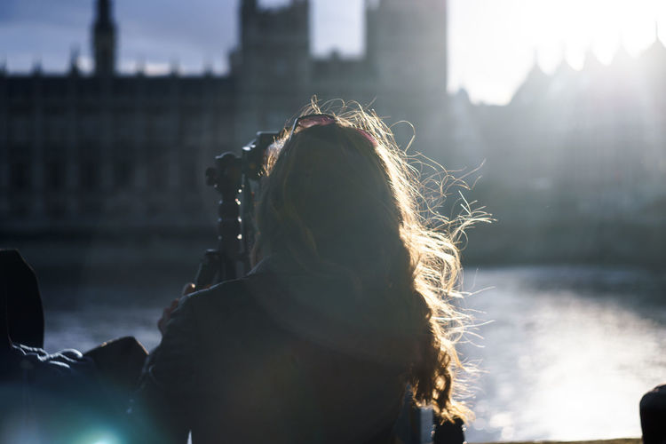 Woman Standing By Thames River Against Houses Of Parliament
