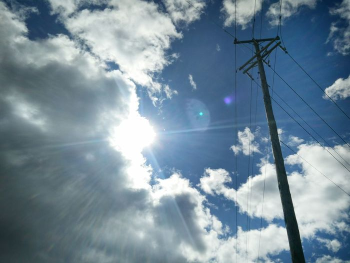 Low angle view of electric pole against bright sky