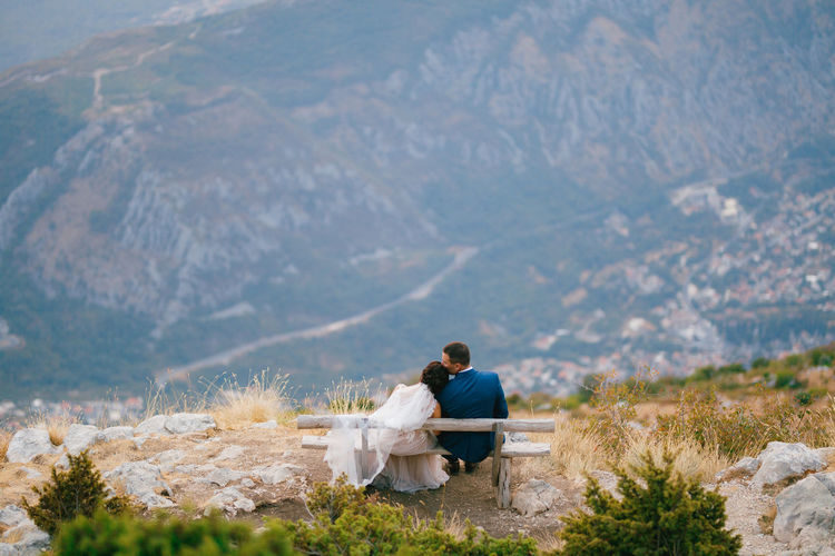 Couple sitting on bench at mountain