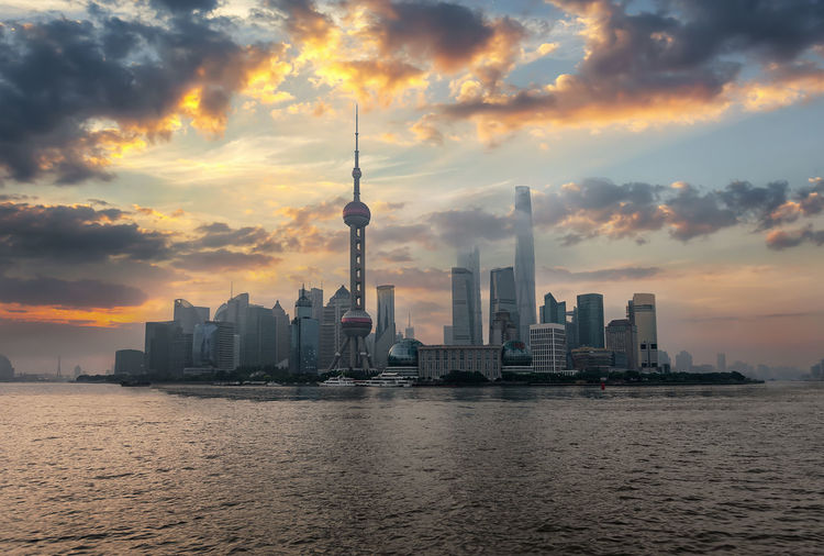 Shanghai at sunrise; the urban skyline with the modern buildings and skyscrapers Architecture Sky Building City Building Exterior Sunset Travel Destinations Urban Skyline Waterfront Cityscape Travel Tall - High Built Structure Skyscraper Financial District  Water Cloud - Sky Outdoors Office Building Exterior Shanghai China Skyline Urban City Sunrise