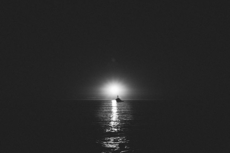 Beacon of Light Beauty In Nature Blackandwhite Boat Cinematic Contrast Film Horizon Over Water Illuminated Light And Shadow Nature Negative Space Outdoors Scenics Sea Silhouette Sunset Tranquil Scene Tranquility Water