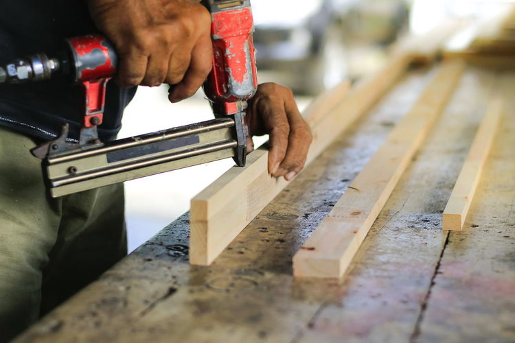 The carpenter is working on the tool. Joiner Nailguns Art And Craft Carpenter Carpenter Tools Craft Focus On Foreground Hand Holding Human Body Part Human Hand Indoors  Joiners Worshop Men Occupation One Person Real People Skill  Wood - Material Work Tool Working Workshop