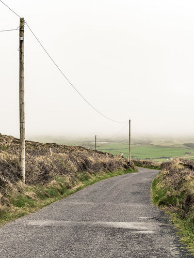 Irish Road Asphalt Beauty In Nature Cable Clear Sky Day Diminishing Perspective Empty Grass Landscape Nature No People Outdoors Road Scenics Sky Telephone Line The Way Forward Tranquil Scene Tranquility Transportation White Line Winding Road