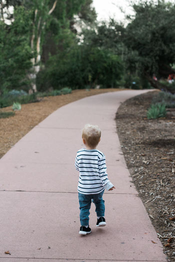 Rear view of boy standing on footpath