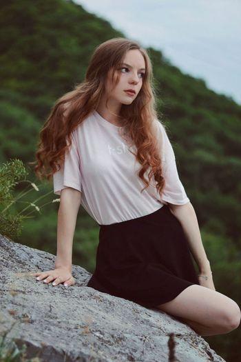 Beautiful young woman sitting on rock