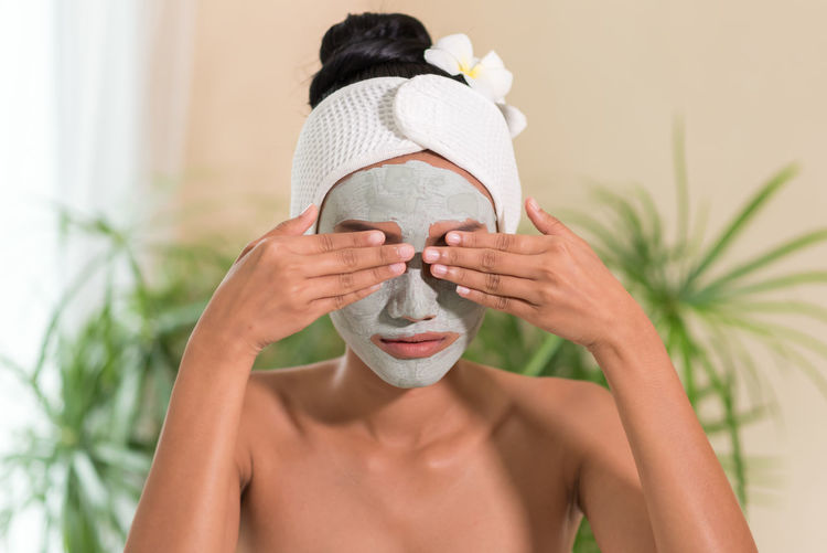 Young woman with facial mask covering eyes in spa