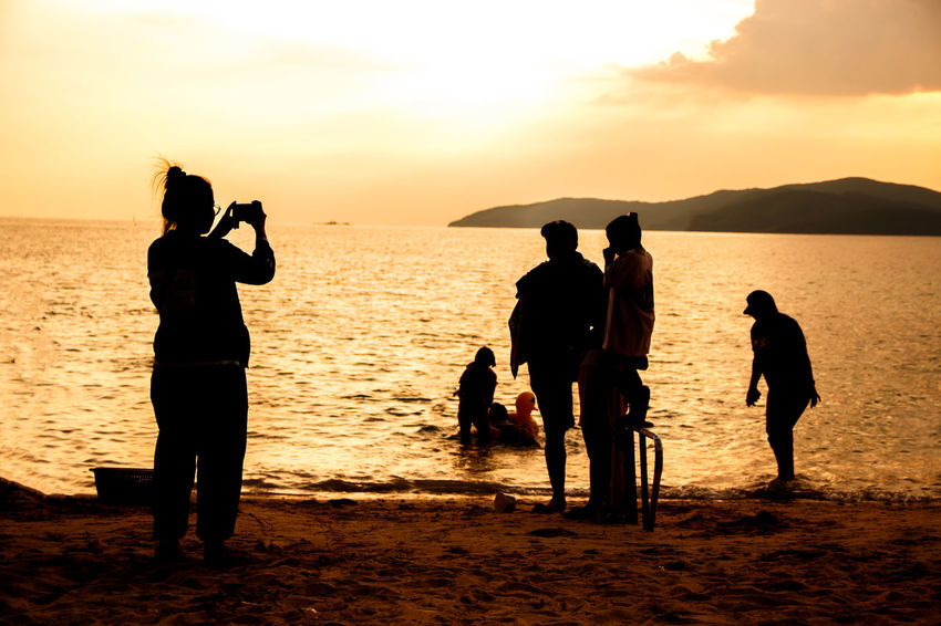 silhouette of people at the beach,The beauty of natural light at sunset. Sky Water Sea Sunset Beach Group Of People Land Real People Scenics - Nature Beauty In Nature Silhouette Lifestyles Men Nature Leisure Activity Women Orange Color Adult Togetherness Horizon Over Water Outdoors Silhouette Happiness Happy People Holiday Relaxing Children Man Romantic Orange Clouds And Sky Love Family Summer Sunrise Boy Freshair Freedom Fun