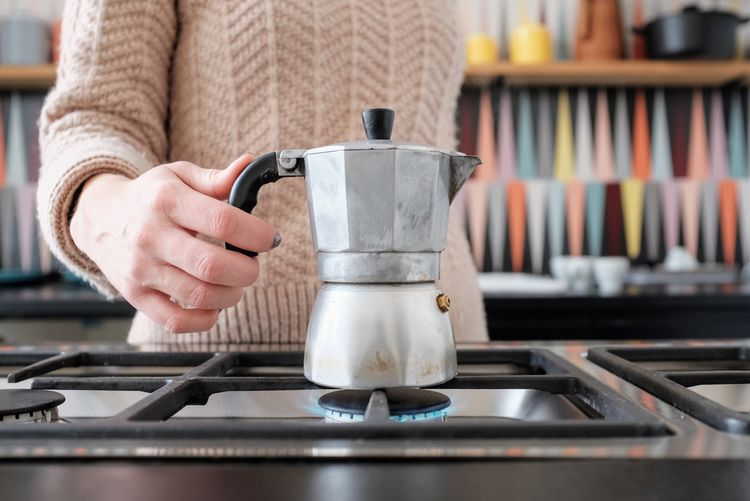Midsection of woman holding espresso maker on gas stove