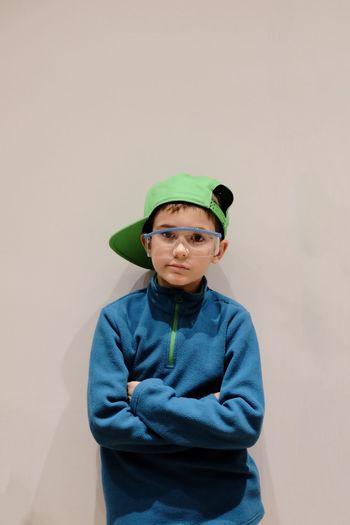 Close-Up Portrait Of Boy Wearing Eyeglasses Against White Background