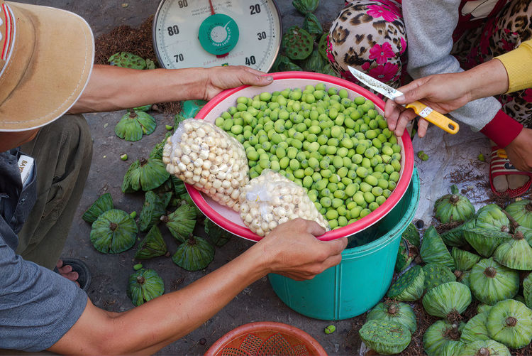Lotus seeds for sale in local market. seller with knife to extract seeds. scales in background.