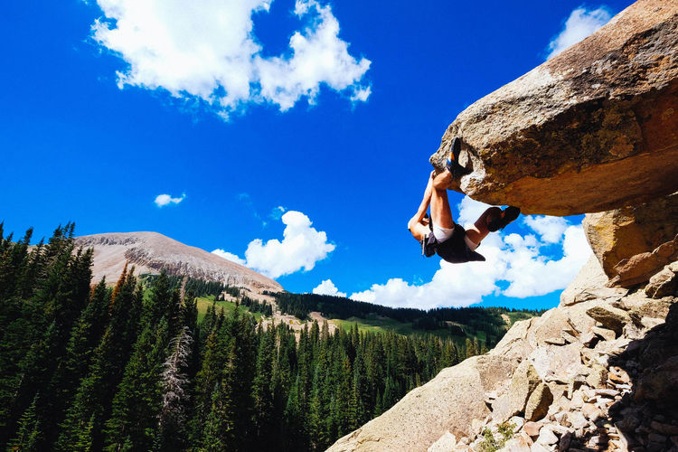 Adventure Beauty In Nature Blue Challenge Cliff Climbing Cloud - Sky Day Extreme Sports Full Length Leisure Activity Lifestyles Mountain Nature One Person Outdoors Physical Geography Real People Rock - Object Rock Climbing Rocky Mountains Sky Strength Sunlight Tree Go Higher