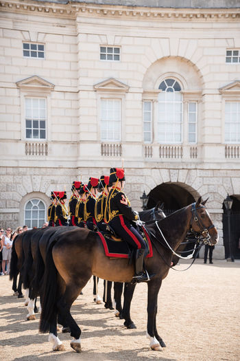 Soldiers riding horses by historic building
