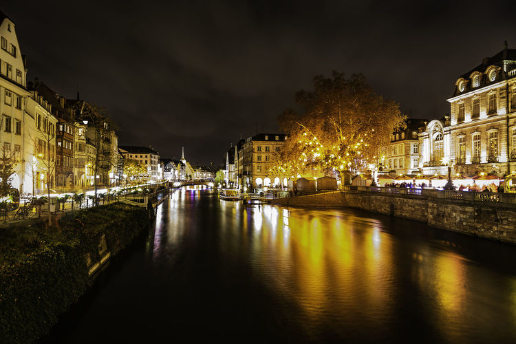 Canal amidst illuminated buildings against sky at night