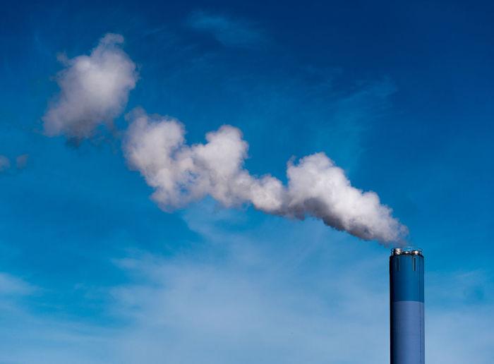 Smoke emitting from chimney against blue sky