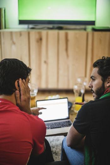 Rear view of man using laptop
