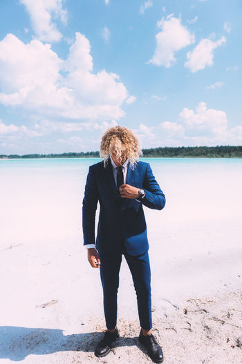 Blond curly man dressed in business suit is posing on the crystal clear lake. Trendy hairstyle, awesome shoot. Summer time. Beach Beauty In Nature Casual Clothing Cloud - Sky Full Length Hairstyle Land Leisure Activity Lifestyles Nature One Person Outdoors Real People Scenics - Nature Sea Sky Standing Tranquil Scene Water