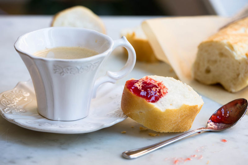 Close-up of coffee and baguette with strawberry jam on table