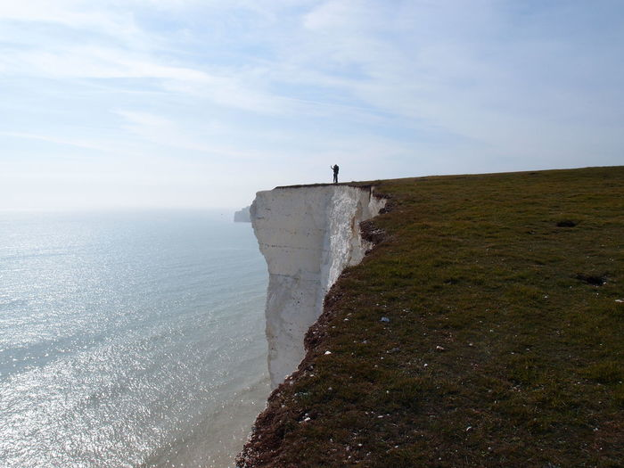 Scenic view of person on cliff against sky