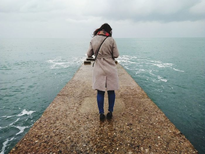 Rear view full length of woman amidst sea on groyne