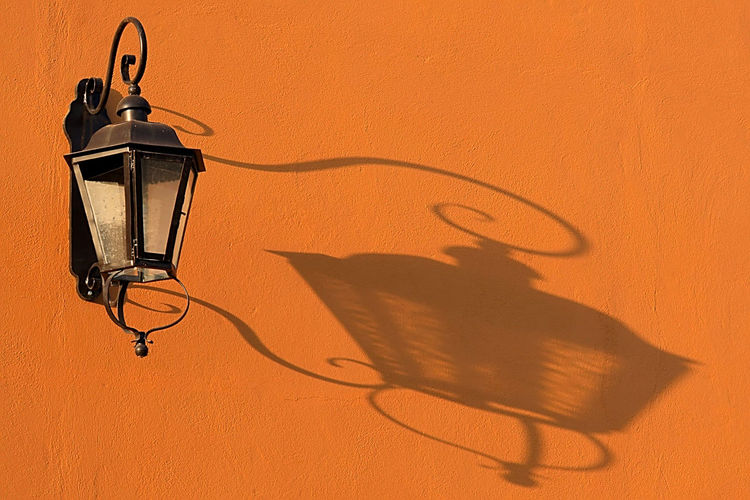 Close-up of electric lamp against orange wall