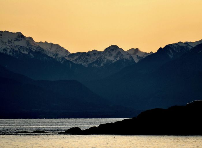 Scenic view of sea and silhouette mountains against sky during sunset