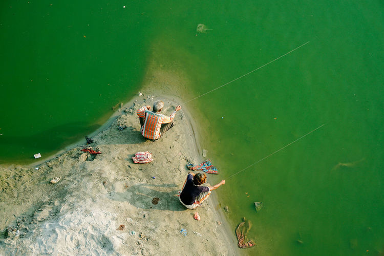 High angle view of boy and man fishing in green river