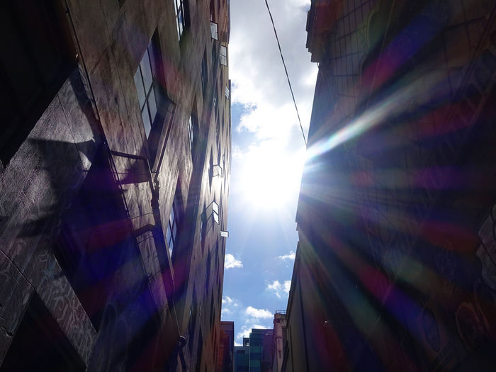 Sunbeams in the blue sky Sky Built Structure Architecture Cloud - Sky Building Exterior Low Angle View Multi Colored No People Nature Day Sunlight Outdoors Building Hanging City Lens Flare Flag Textile Residential District Window Apartment
