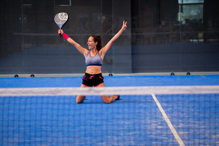 Portrait of beautiful young wimmer girl exulting on indoor padel tennis court