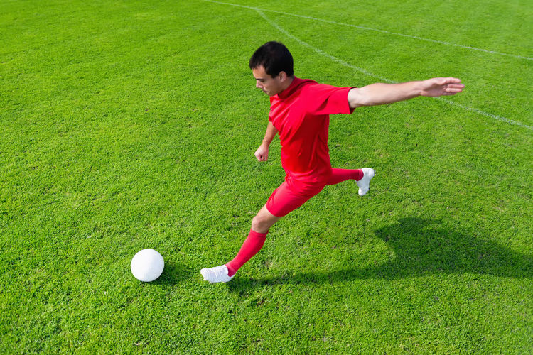 High Angle View Of Man Kicking Soccer Ball On Field During Sunny Day