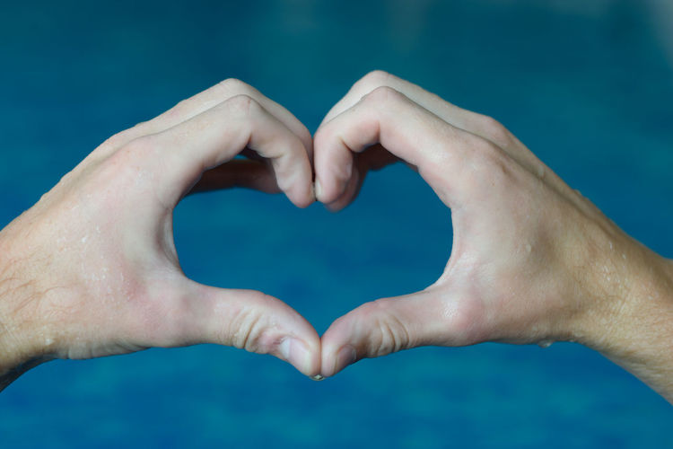 Cropped hands making heart shape against swimming pool