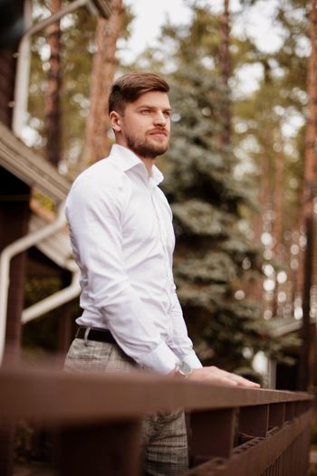 Young man looking away while standing by railing against trees in forest