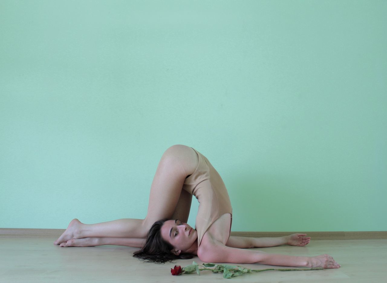 Young woman exercising against blue wall