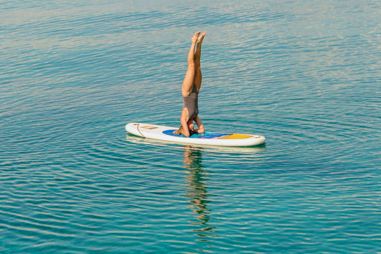 Full length of woman doing headstand on surfboard in sea