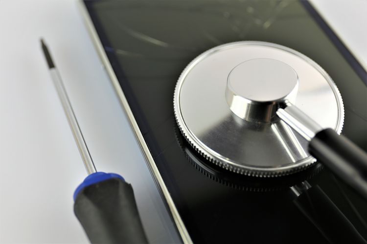 Close-Up Of Stethoscope On Mobile Phone With Screwdriver Over White Background