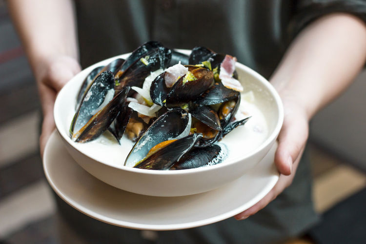 Midsection Of Person Holding Mussels In Bowl