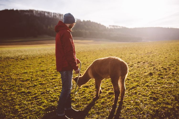 Man with animal standing on field