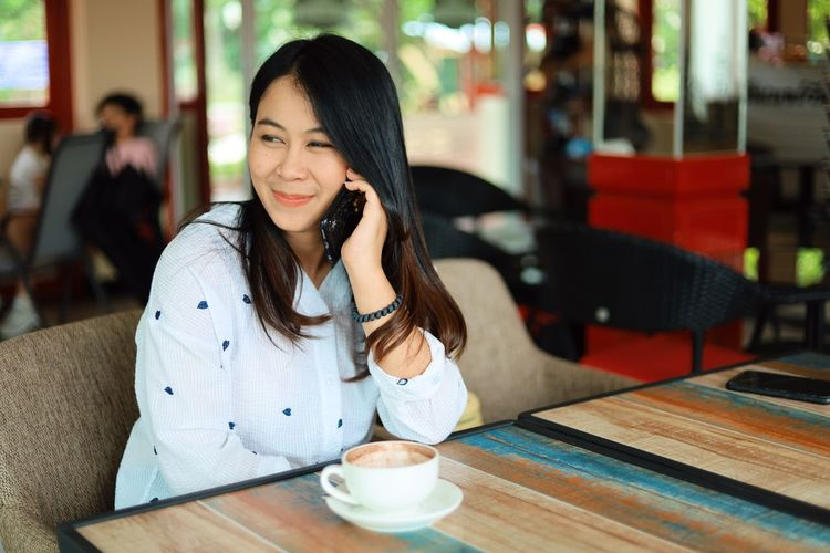 Drink Food And Drink Table Cafe Restaurant Cup Sitting Coffee - Drink Smiling Coffee One Person Coffee Cup Women Mug Young Adult Happiness Waist Up Mobile Phone Refreshment Adult Hair Wireless Technology Hairstyle Beautiful Woman