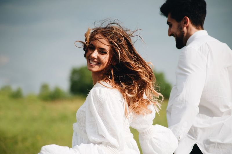 Close-Up Portrait Of Smiling Woman With Man Walking Against Sky