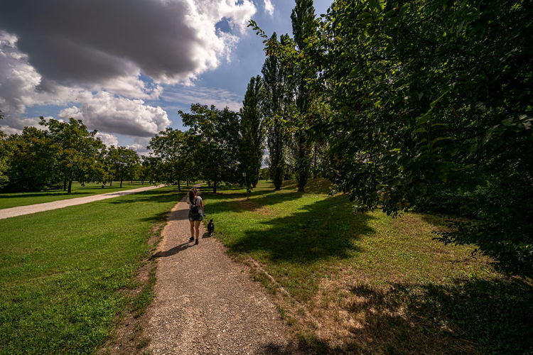 Rear view of woman walking with dog on footpath