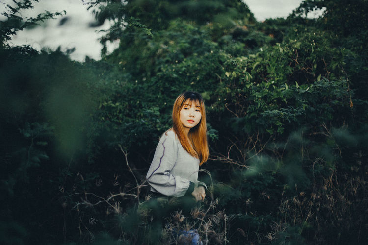 Portrait of young woman standing on field in forest